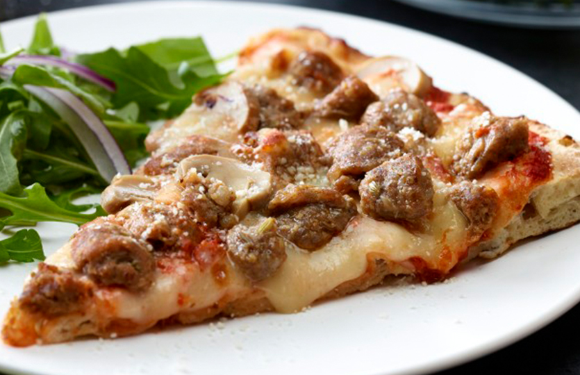 Sausage pizza slice on white plate