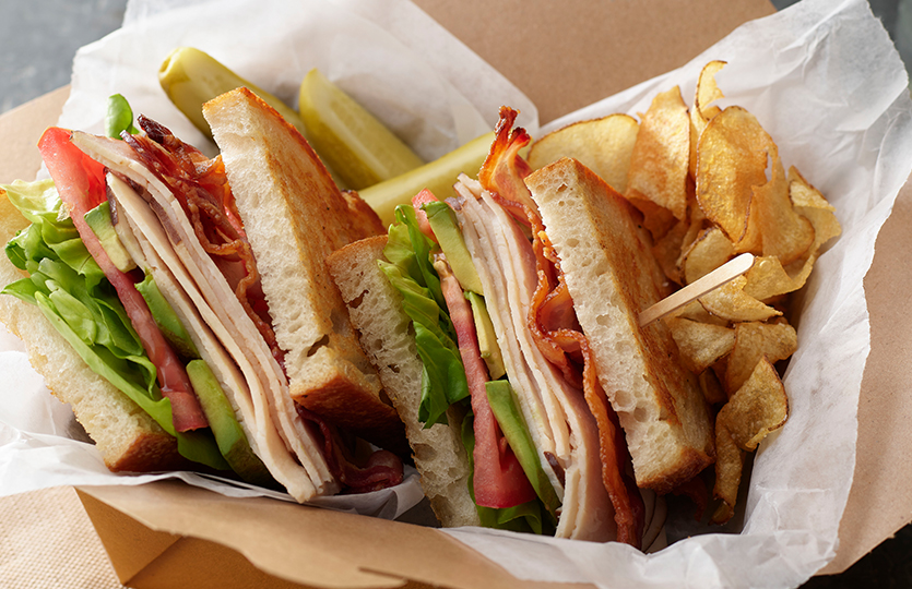 Turkey and Cheese sandwich in basket with chips