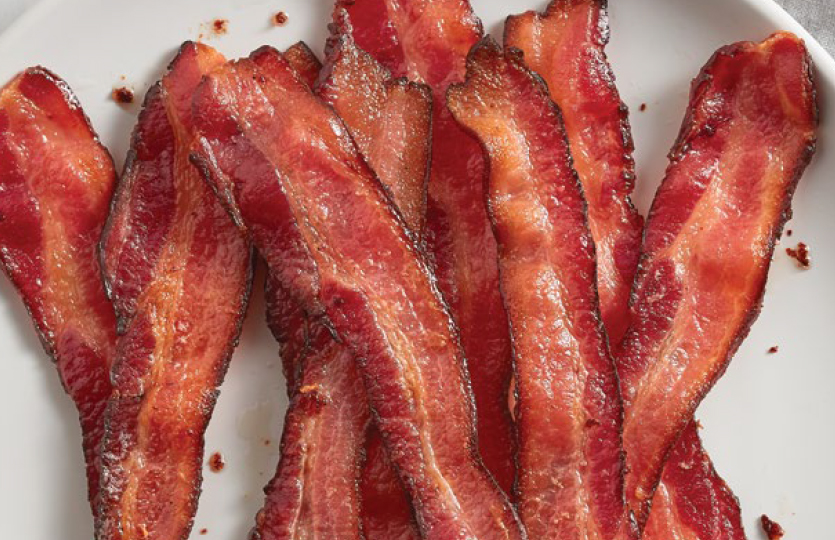 Cooked bacon slices on white plate